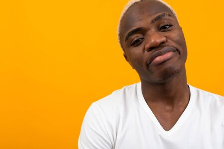 portrait of displeased african black man on yellow background with copy space. Imagens