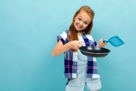 Teenager caucasian girl is going to fry something with a pan isolated on blue background. Imagens
