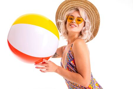 Cheerful blonde caucasian female stands in swimsuit, hat with big rubber ball and smiles isolated on white background
