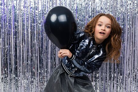 smiling attractive cute stylish caucasian girl in shiny clothes holding a black balloon on a festive tinsel background. Imagens