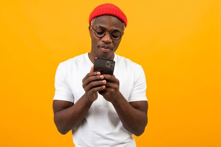 handsome african man in a white t-shirt communicates on a social network in a telephone on a yellow studio background.