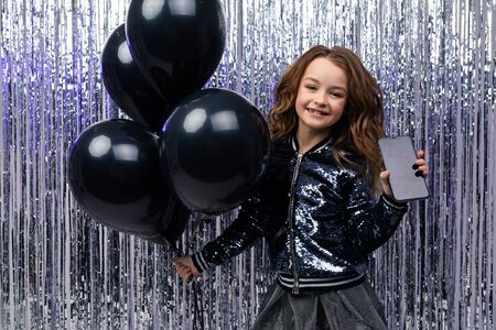 girl in a festive mood holds a smartphone with a layout and helium balloons on a background of tinsel. black Friday.