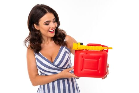 sexy girl in a dress holds a red canister with fuel gasoline on a white background with copy space.