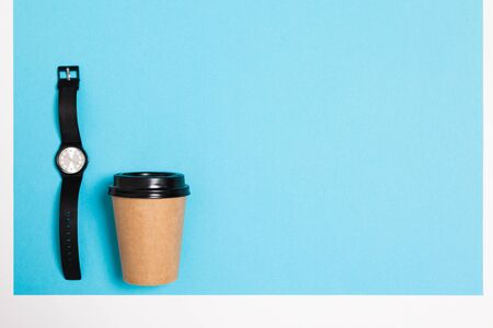 minimalism concept. paper cup and watch on a blue background with copy space. Reklamní fotografie