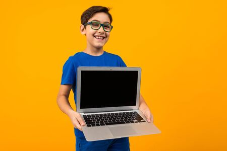 caucasian boy holds laptop screen forward with mock up on yellow studio background with copy space.