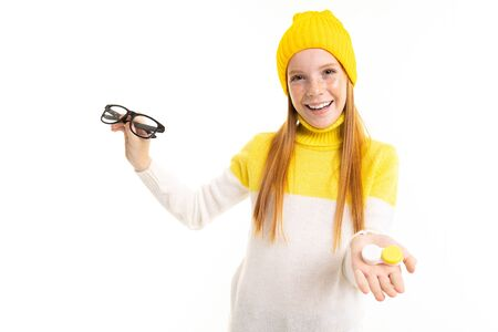 Happy teenager girl with red hair, hoody and hat holds a glasses isolated on white background.
