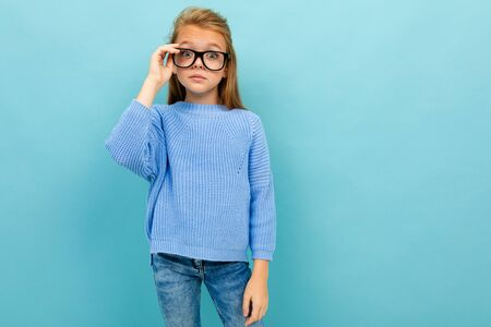 Teenager caucasian girl with long brown hair and glasses, isolated on blue background