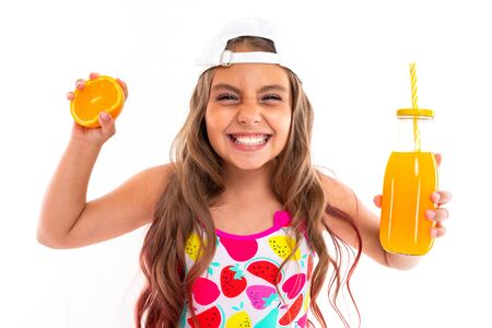 tanned girl squeezes an orange and holds a glass of juice on a white background.
