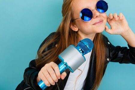 Young female with brown hair in black jacket, blue sunglasses with blue microphone isolated on blue background Reklamní fotografie
