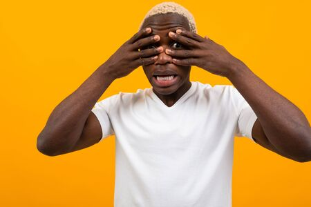 black african young man covers his face with his hands on a yellow background.