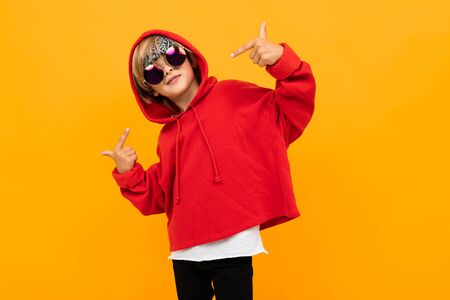 Portrait of stylish young caucasian boy with medium fair hair in red sweatshirt, black trousers and white t-shirt with sunglasses dances isolated on yellow background