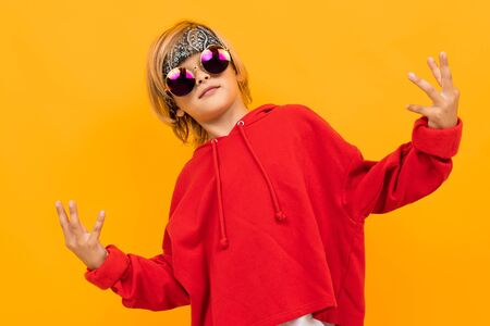 Portrait of stylish young caucasian boy with medium fair hair in red sweatshirt, black trousers and white t-shirt with sunglasses isolated on yellow background