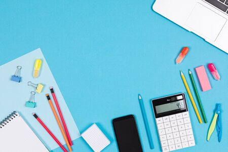Calculator, laptop, mobile phone, notes, pens, pencils, ruler, eraser, compass isolated on blue and white background