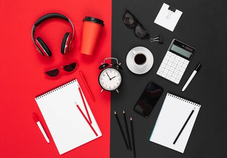 Desktop with earphones, alrm clock, phone, pens, pencils, note, coffee isolated on red and black background.