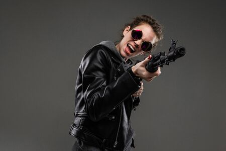 black friday concept. attractive stylish caucasian girl in a black leather jacket and a gray hoody and sunglasses stands with a gun on a dark gray background.