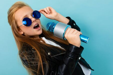 Teenager in black jacket, blue sunglasses sings songs with blue microphone isolated on blue background Foto de archivo - 140648787
