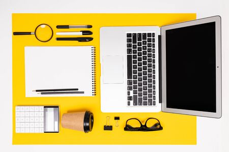 office workplace. top view of stationery with laptop, notepads, magnifier and calculator on yellow surface. Reklamní fotografie