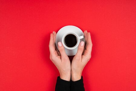 Hands holds a cup of coffee isolated on red background.
