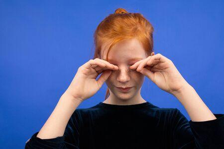 girl rubs her eyes due to dryness on a blue background. Reklamní fotografie