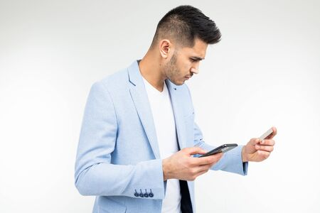 a man enters data with a credit card into a mobile phone to make a purchase via the Internet on a white background.