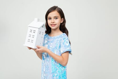 teenager girl with a paper bag at home on a white background with copy space. immovable property. Imagens