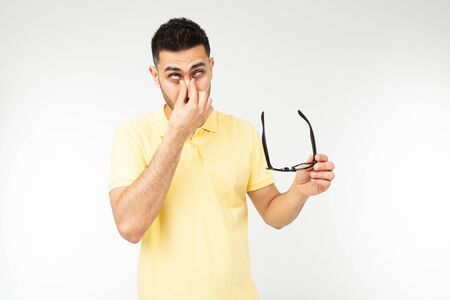 guy has dry eyes taking off glasses on a white background.