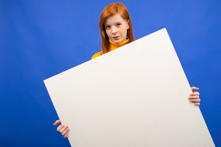 european red-haired teenage girl holding a white sheet of paper with a mockup for advertising on a blue studio background.