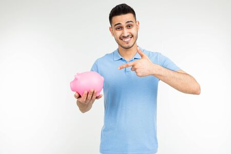 brutal man in a blue shirt holds a piggy bank and points a finger at it on a white background with copy space. Stockfoto
