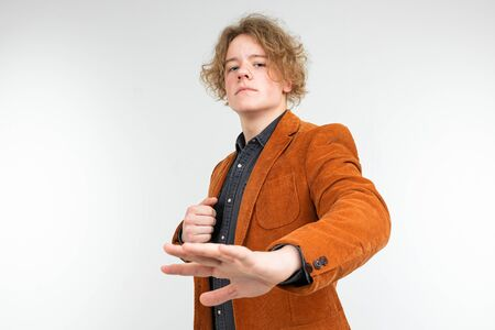 confident curly blond guy in a brown jacket waves his hands away on a white studio background.