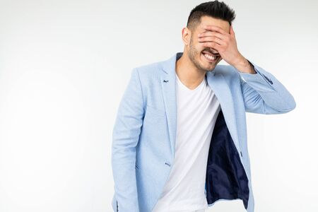 man in a blue jacket covers his face with shame with his hands on a white studio background.
