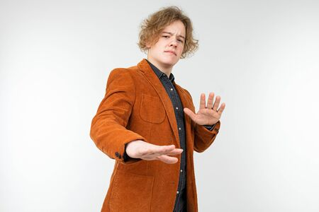confident curly blond guy in a brown jacket with arms crossed refuses on a white studio background. Reklamní fotografie