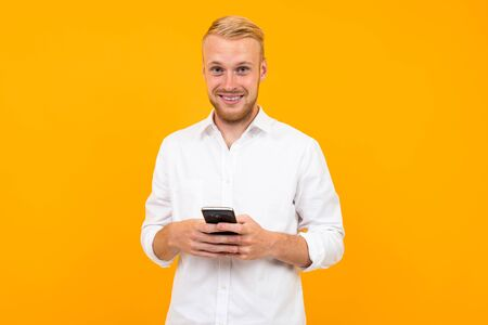 guy in a white t-shirt with a cell phone in his hand.