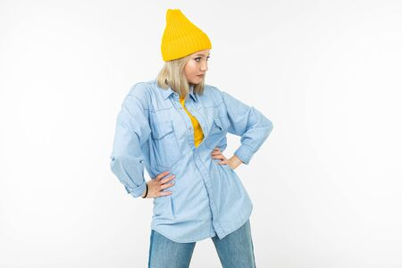 blond girl in a stylish denim shirt and a yellow sweater on a white background with copy space.