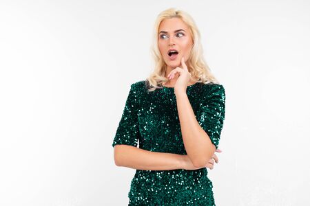 surprised blonde girl in a green elegant dress on a white background with copy space. Zdjęcie Seryjne