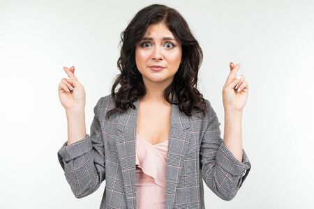 girl in a classic checkered gray jacket crossed her fingers on a white background.