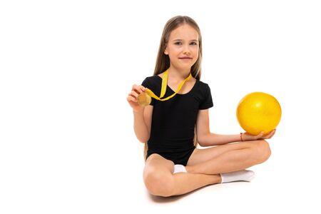 winner girl gymnast sitting on the floor with gymnastic ball on a white background with copy space. Zdjęcie Seryjne