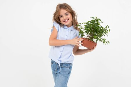 teenage gardener girl holding a houseplant with green leaves on a white background with copy space.