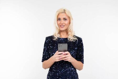 close-up of a beautiful charming woman in a shiny dress sitting on the phone on a white background with copy space.