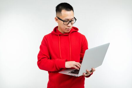 attractive brunette man in casual red hoodie with a laptop in his hands on a white studio background.