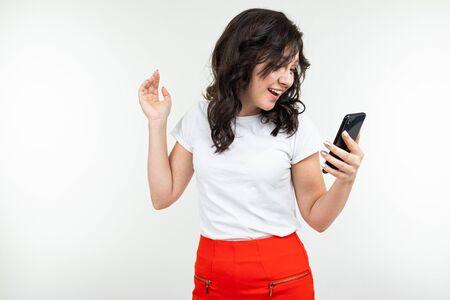 cute girl talking on the speakerphone of a phone on a white studio background. Zdjęcie Seryjne