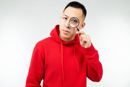 brunette man in red hoody looks at the camera through a magnifier on a white isolated background.