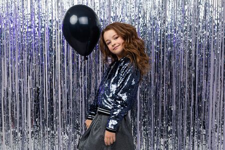 smiling attractive cute stylish caucasian girl holding a black balloon on a festive background. Zdjęcie Seryjne