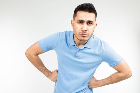 Caucasian handsome guy in a blue T-shirt stood in a pose and is not inferior on a white studio background.