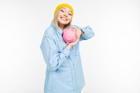 stylish girl in a blue shirt with a bank for saving finances on a white background with copy space. Zdjęcie Seryjne