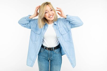 portrait of a joyful happy girl in jeans clothes showing emotions of joy on a white studio background.