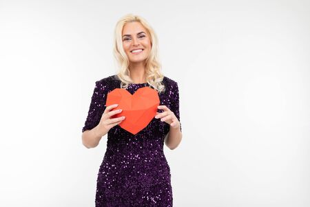 happy dreaming lady in purple dress holding paper red heart on white background with copy space. Zdjęcie Seryjne