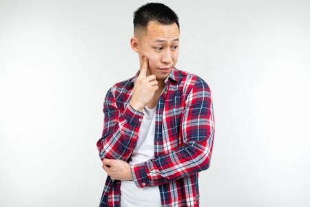 Confident Asian man in a plaid shirt wide open on a white studio background with copy space.