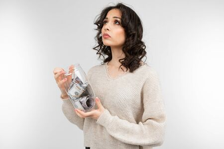 girl dreams of spending her money from a piggy bank on a white background.