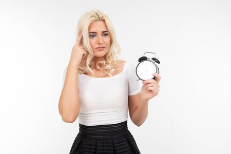sexy lady in a white t-shirt holds an alarm clock with a large dial on a white background with copy space.
