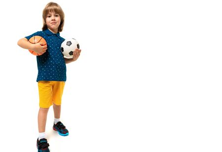 sport winner boy holding a soccer and basketball ball in his hands on a white background with copy space.